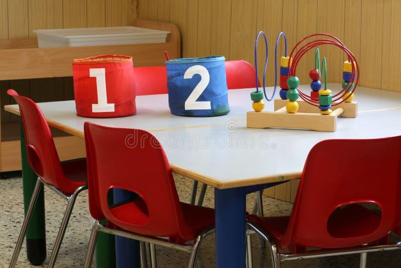 Zwei Gläser in der Schule setzen in einem Kindergarten für Kinder auf die Bank lizenzfreie stockfotografie