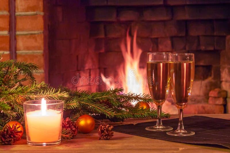 Zwei Gläser des Champagners, der Dekorationen, der Weihnachtsbaumaste und der Kerze auf einem Holztisch vor einem Brennen lizenzfreie stockfotos