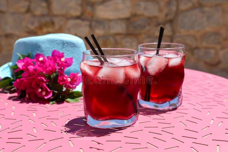 Zwei Gläser des roten Cocktails des Sommers mit Eis nahe bei einem blauen Hut und des Zweigs der Bouganvillablumen auf einer rosa lizenzfreie stockbilder