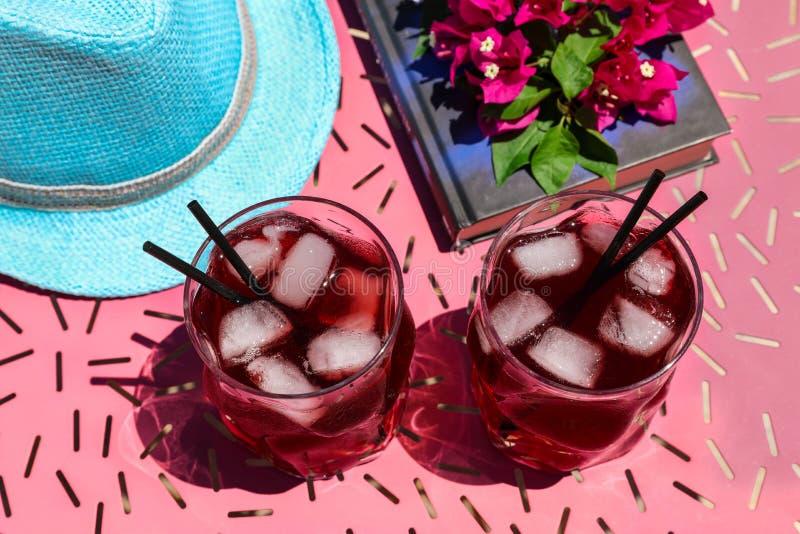 Zwei Gläser des roten Cocktails des Sommers mit Eis nahe bei einem Buch, ein Zweig des Bouganvillas blüht, blauer Hut auf einer r lizenzfreies stockbild