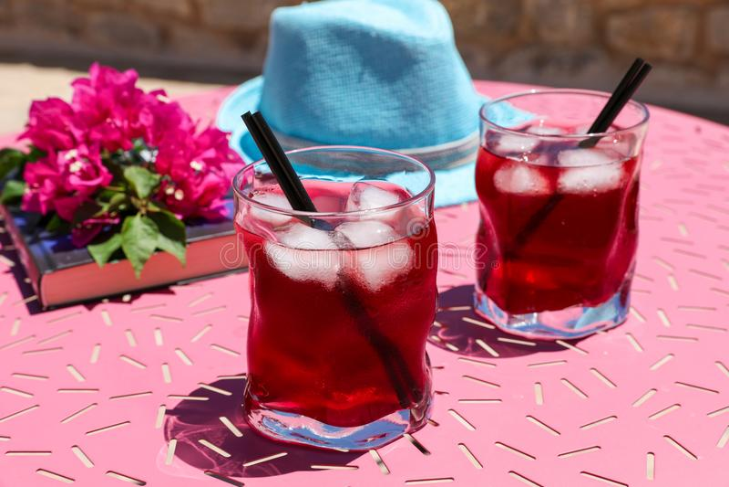 Zwei Gläser des roten Cocktails des Sommers mit Eis nahe bei einem Buch, ein Zweig des Bouganvillas blüht, blauer Hut auf einer r lizenzfreie stockbilder