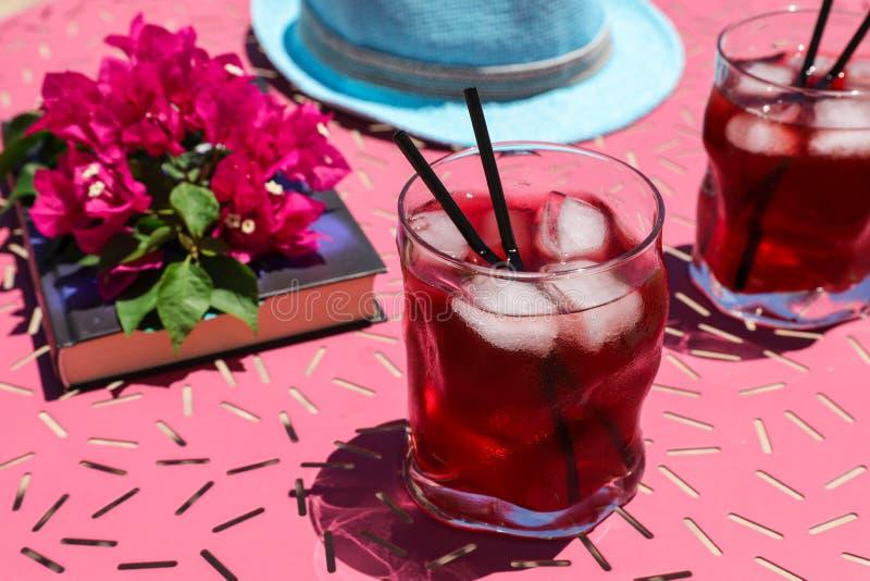 Zwei Gläser des roten Cocktails des Sommers mit Eis nahe bei einem Buch, ein Zweig des Bouganvillas blüht, blauer Hut auf einer r lizenzfreies stockfoto