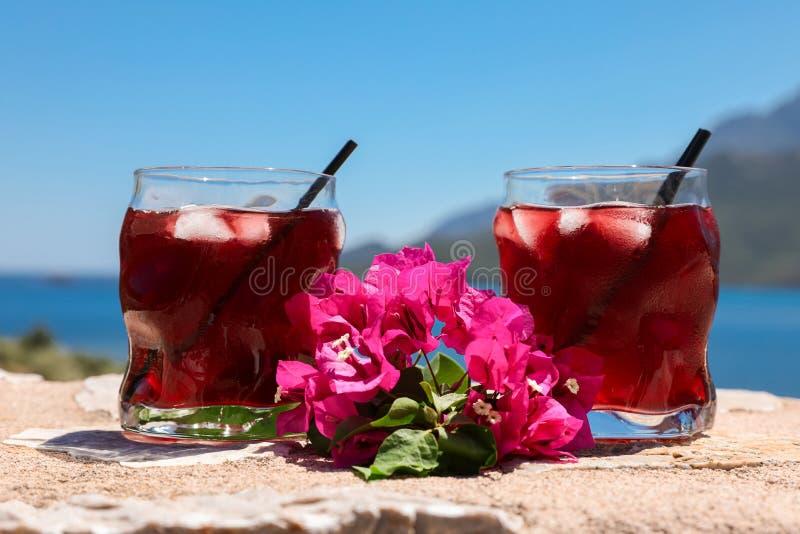 Zwei Gläser des roten Cocktails des Sommers mit Eis und des Zweigs der Bouganvillablumen zwischen auf dem Hintergrund des blauen  stockfotografie