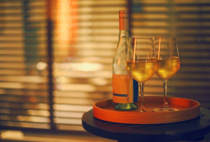 Zwei Gl?ser des Wei?weins und der Flasche im Restaurant auf unscharfem Hintergrund stockfoto