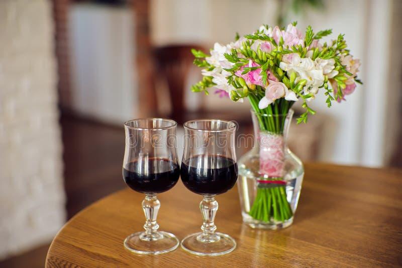 Zwei Gläser des Weins und des Blumenstraußes lizenzfreie stockfotografie