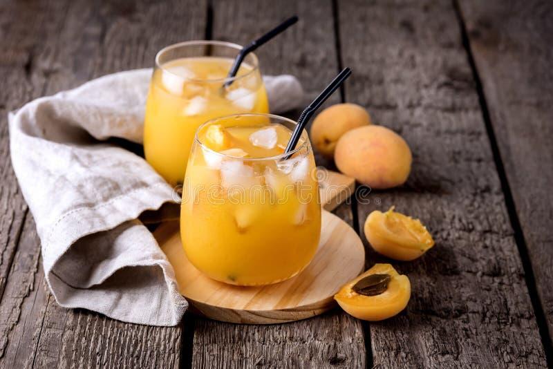 Zwei Gläser frischer geschmackvoller Aprikosen-Saft auf dem hölzerner Hintergrund-horizontalen gesunde Diät-Getränk-Kopien-Raum lizenzfreie stockfotos