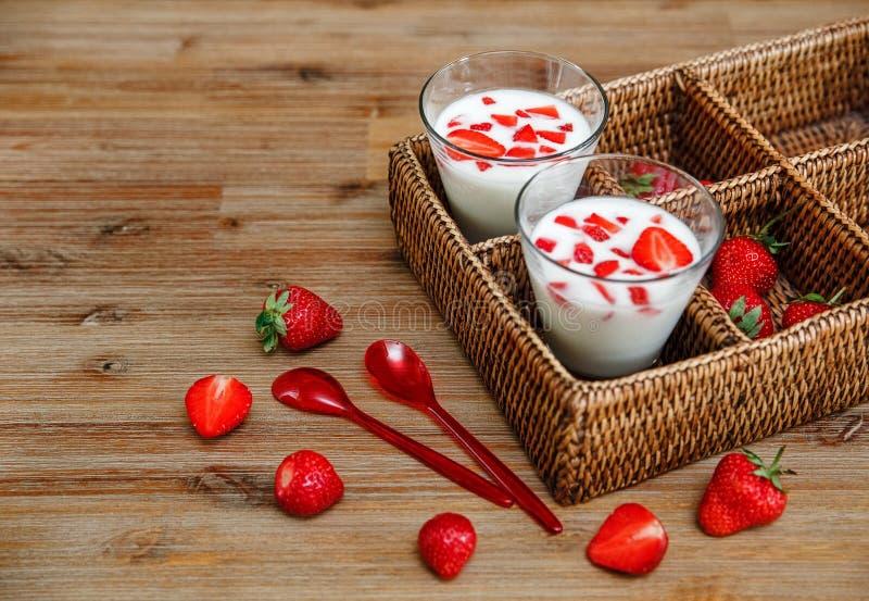 Zwei Gläser Jogurt, rote frische Erdbeeren im Rattan-Kasten mit Plastiklöffeln auf dem Holztisch Frühstück organische gesunde T stockbilder