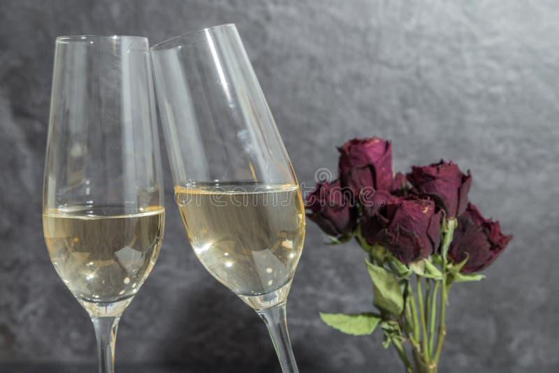 Zwei Gläser mit Champagner mit einem Blumenstrauß mit getrockneten roten Rosen lizenzfreie stockbilder