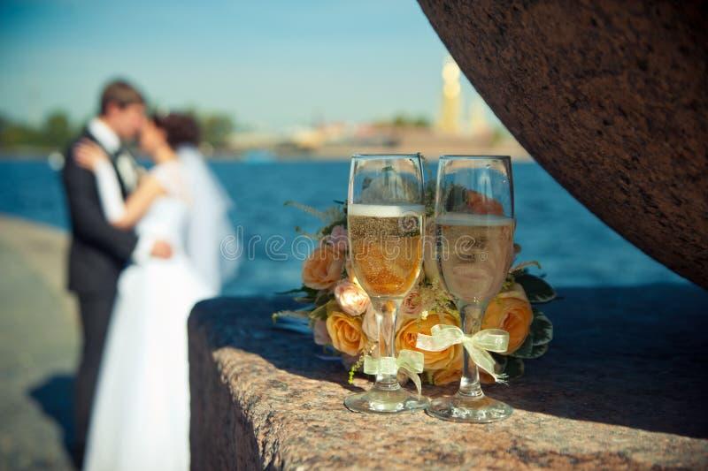 Zwei Gläser mit Champagner und einem Blumenstrauß von Rosen auf einem backgroun stockfotografie