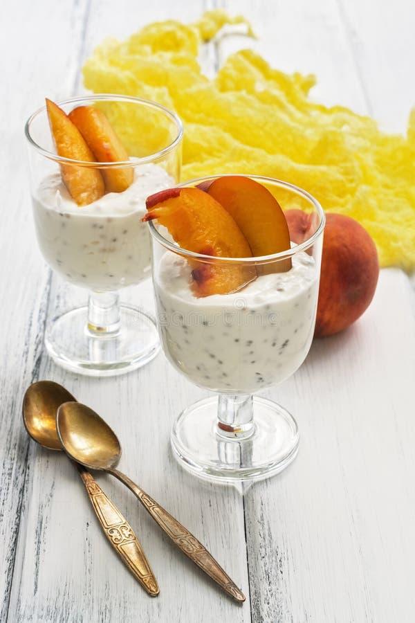 Zwei Gläser mit einem nützlichen Jogurt mit chia Samen und Pfirsichscheiben auf einer weißen hölzernen rustikalen Tabelle Selekti stockfotografie