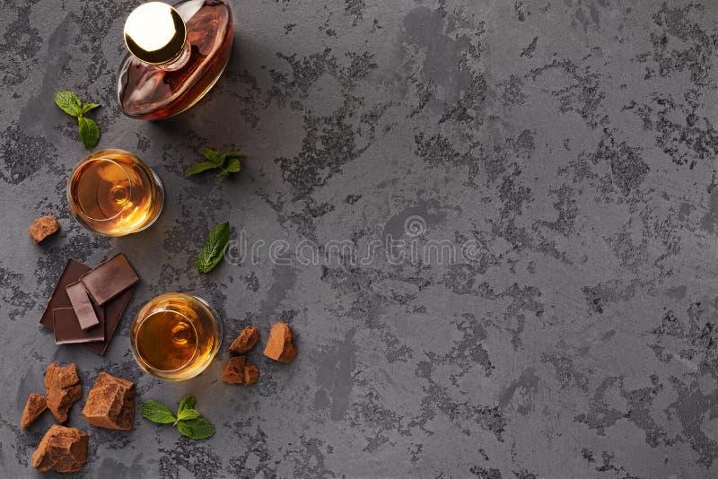 Zwei Gläser mit Kognak, Whiskysteinen und Schokolade lizenzfreie stockfotos