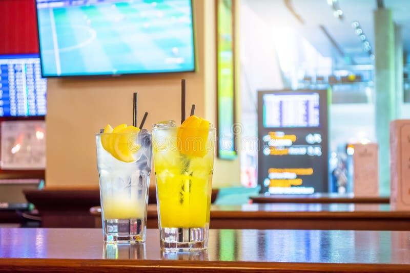 Zwei Gläser mit Limonade - Zitrone, orange Im Hintergrund, in einem Schirm mit Fernsehfußball und in den on-line-Anzeigetafelflüg lizenzfreie stockfotografie