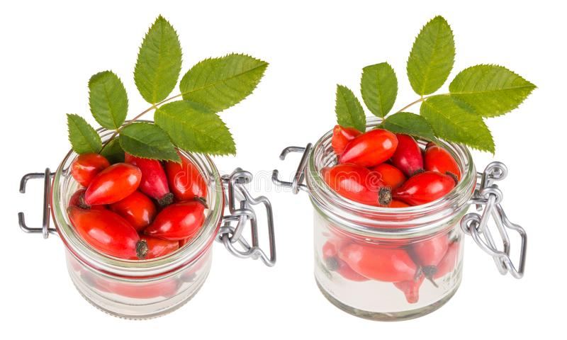 Zwei Gläser mit roten Hagebutten und Grünblättern lizenzfreies stockbild
