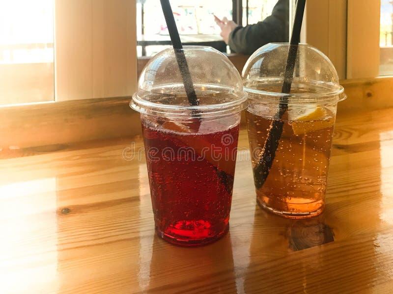 Zwei Gläser rote und gelbe erneuernde kalte geschmackvolle süße Himbeererdbeerkirschorange Pfirsichzitronen-Fruchtplastiklimonade stockbild