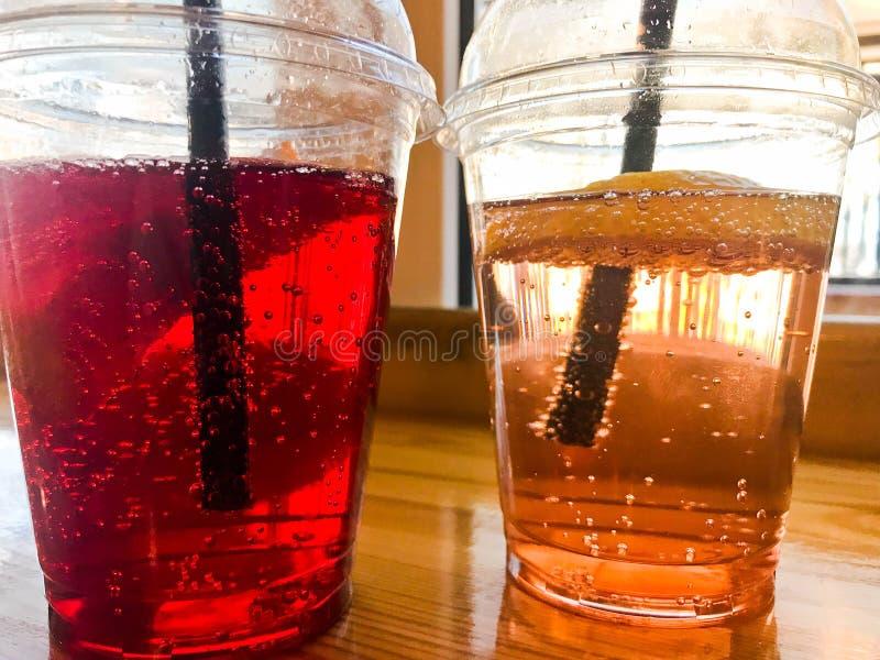 Zwei Gläser rote und gelbe erneuernde kalte geschmackvolle süße Himbeererdbeerkirschorange Pfirsichzitronen-Fruchtplastiklimonade stockfotos