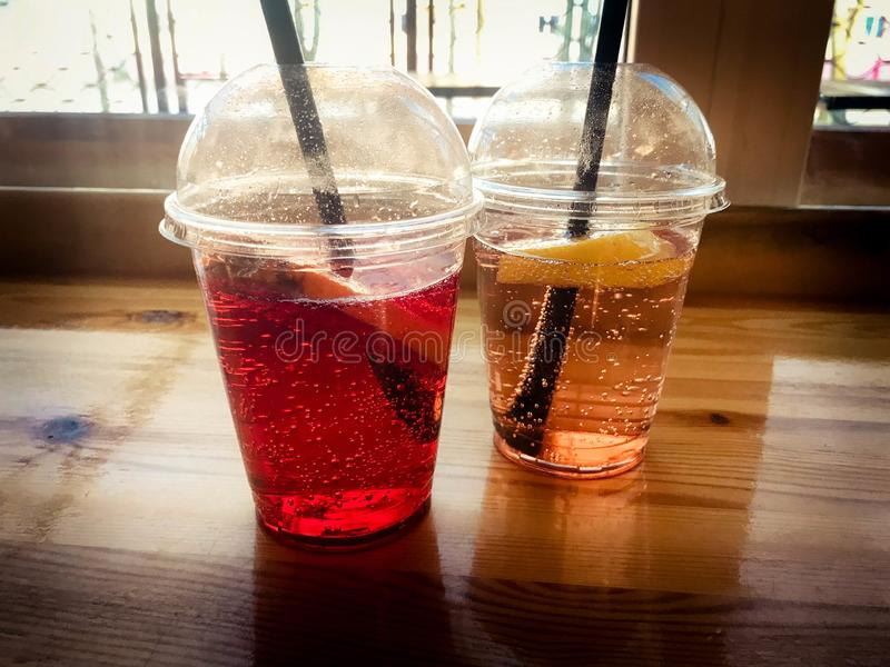 Zwei Gläser rote und gelbe erneuernde kalte geschmackvolle süße Himbeererdbeerkirschorange Pfirsichzitronen-Fruchtplastiklimonade stockfotografie