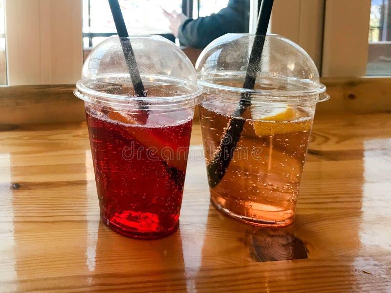 Zwei Gläser rote und gelbe erneuernde kalte geschmackvolle süße Himbeererdbeerkirschorange Pfirsichzitronen-Fruchtplastiklimonade lizenzfreie stockfotos