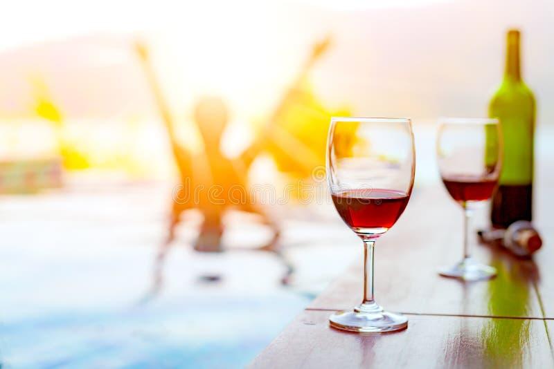 Zwei Gläser Rotwein nahe Swimmingpool mit einem Mann schwimmt im Pool stockfoto