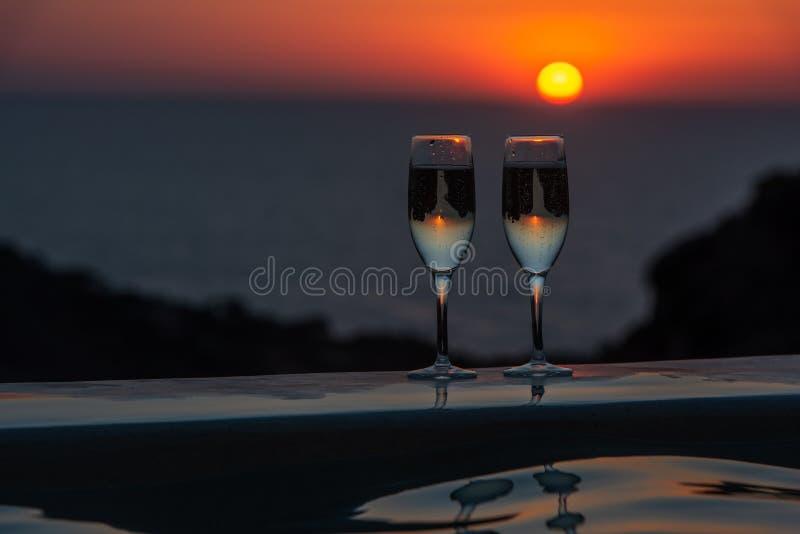 Zwei Gläser Sekt durch das Pool auf einem Sonnenunterganghintergrund stockfotografie