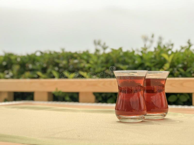 Zwei Gläser türkischer Tee in der traditionellen Schale auf Holztisch stockbild
