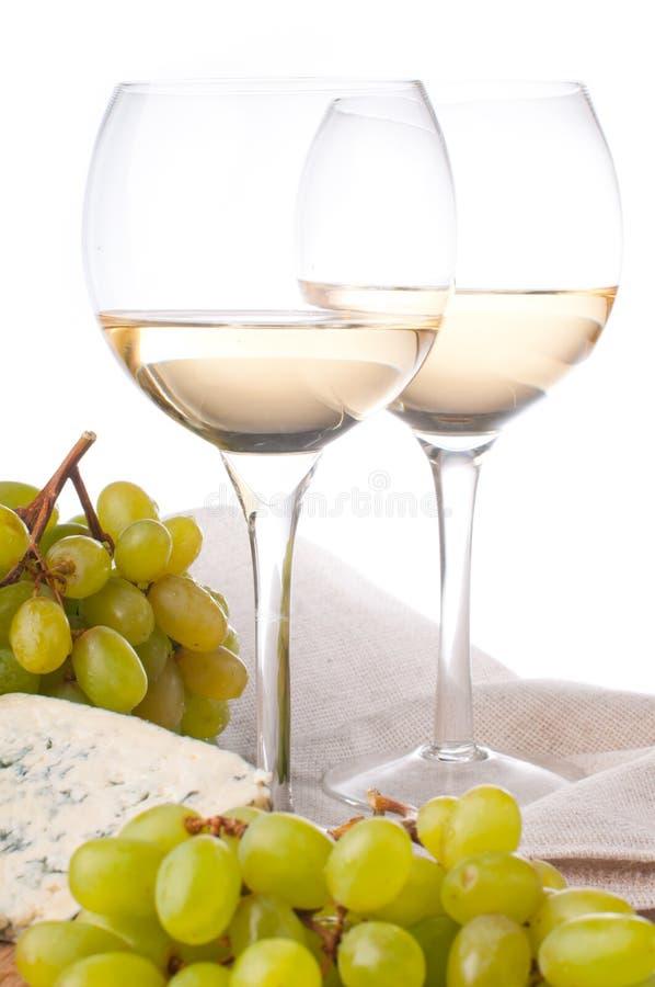 Zwei Gläser weißer Wein, Käse und Trauben lizenzfreie stockbilder