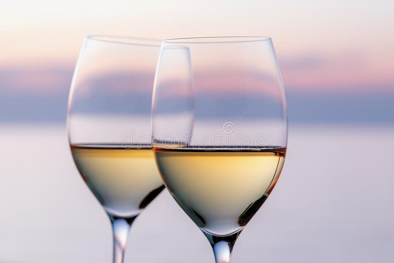 Zwei Gläser Weißwein gegen den Abendhimmel stockfotografie