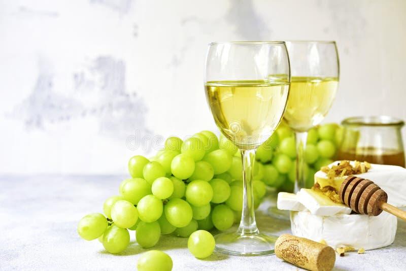 Zwei Gläser Weißwein, Käse und Trauben stockfoto