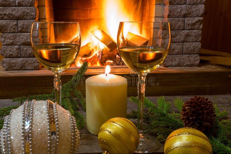 Zwei Gläser Weißwein, Kerze, Weihnachtsglaskugeln, nahe gemütlichem firepace lizenzfreie stockfotografie