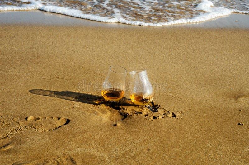 Zwei Gläser Whisky sondern Malz auf dem Sand aus, der durch das wav gewaschen wird stockfotografie