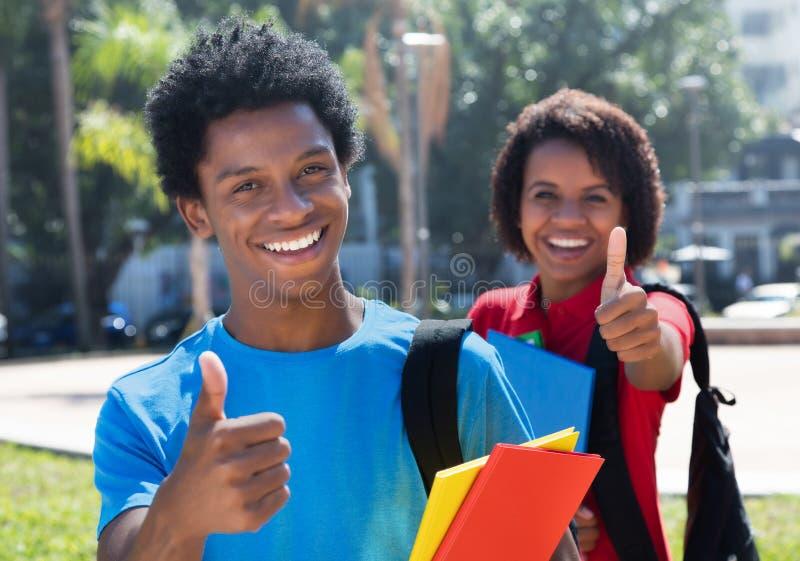 Zwei glückliche Afroamerikanerstudenten auf dem Campus, die Daumen zeigen stockfotos