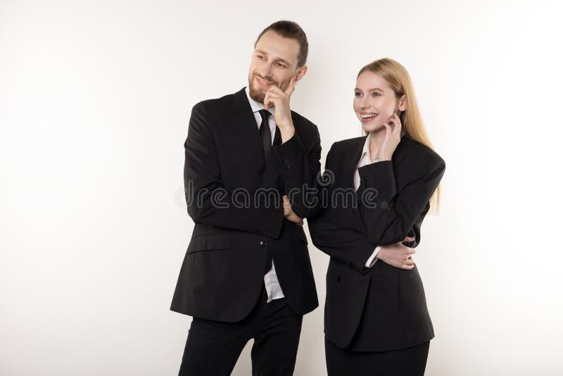 Zwei glückliche Angestellte in den schwarzen Anzügen, die zusammen mit Händen auf der Taille betrachtet die Darstellung ihres Che lizenzfreies stockbild