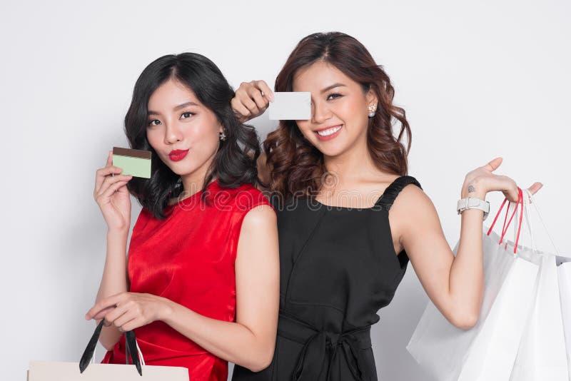 Zwei glückliche attraktive junge Frauen mit der Kreditkarte, die shoppi hält lizenzfreie stockbilder