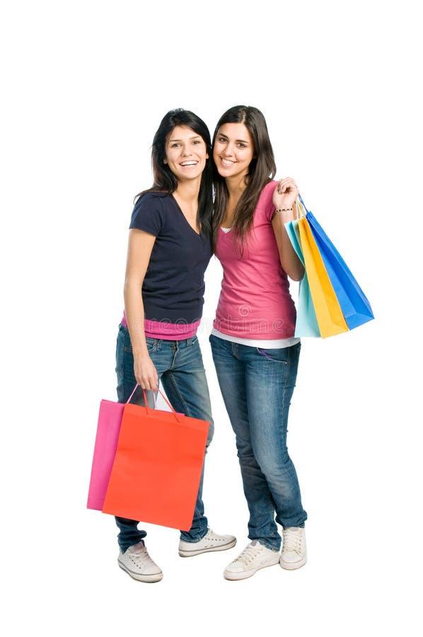 Zwei glückliche Brunettemädchen, die das Einkaufen tun stockfoto