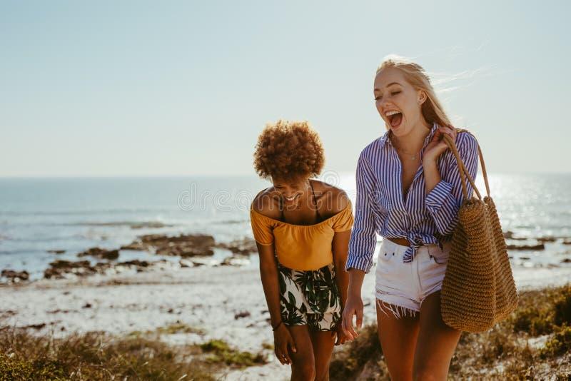 Zwei glückliche Frauen, die entlang den Strand gehen stockfoto