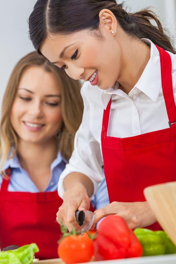 Zwei glückliche Frauen, die Lebensmittel in einer Küche zubereitend kochen stockfoto