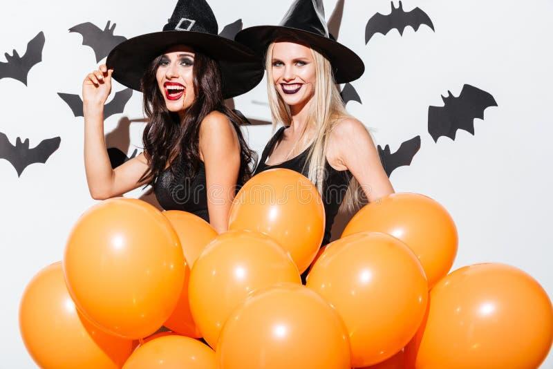 Zwei glückliche Frauen in Hexenhalloween-Kostümen mit orange Ballonen lizenzfreie stockbilder