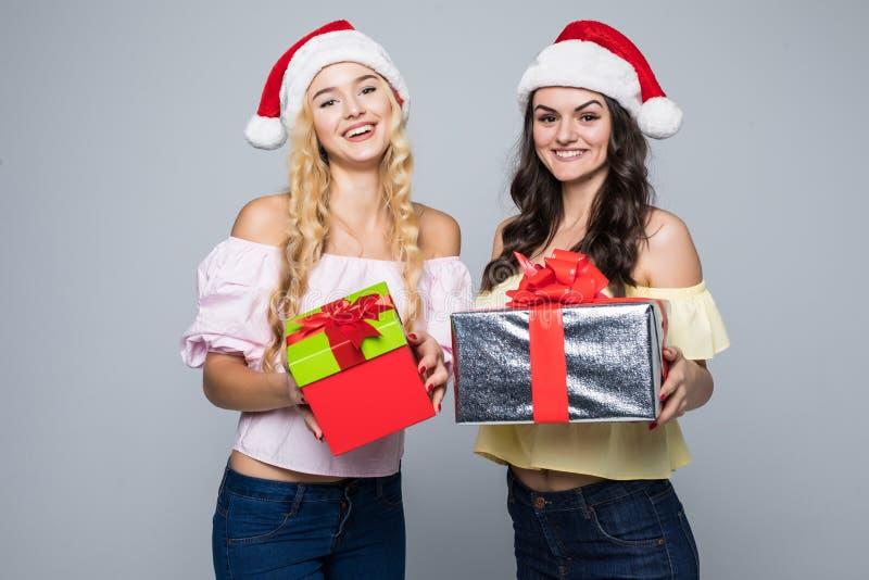 Zwei glückliche Frauen in Sankt-Hüten mit den Geschenkboxen, die auf weißem Hintergrund stehen lizenzfreie stockfotografie