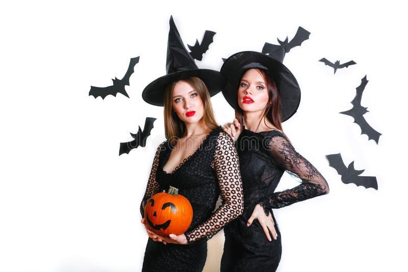 Zwei glückliche Frauen in schwarzen Hexenhalloween-Kostümen mit Kürbis auf Partei über weißem Hintergrund lizenzfreies stockbild
