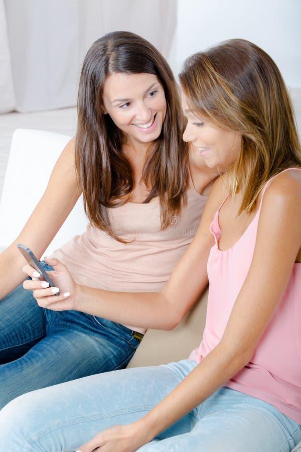 Zwei glückliche Freunde, die Medieninhalt im intelligenten Telefon aufpassen stockbilder