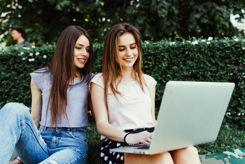 Zwei glückliche Freunde, die online in einem Laptop sitzt auf dem Gras in der Straße suchen stockbild