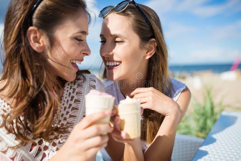 Zwei glückliche Freundinnen, die draußen Eiscreme essen stockbild