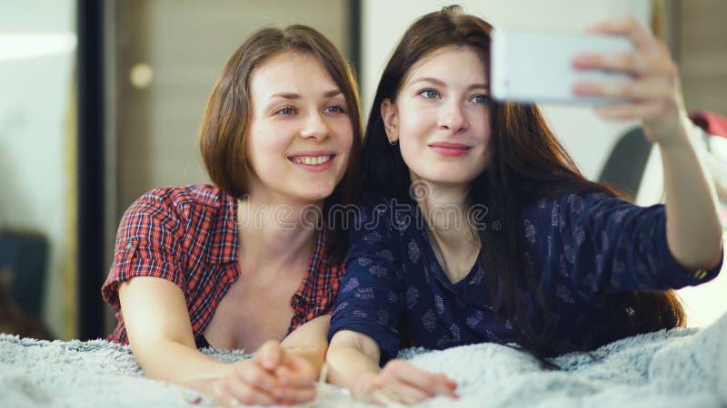 Zwei glückliche Freundinnen, die im Bett liegen und selfie am Morgen machen und haben Spaß auf Bett lizenzfreie stockbilder