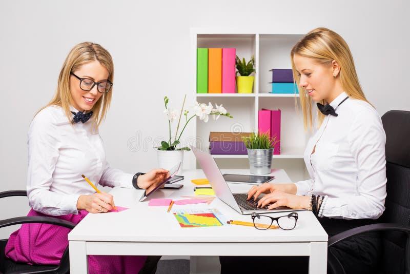 Zwei glückliche Geschäftsfrauen, die im Team arbeiten stockbilder