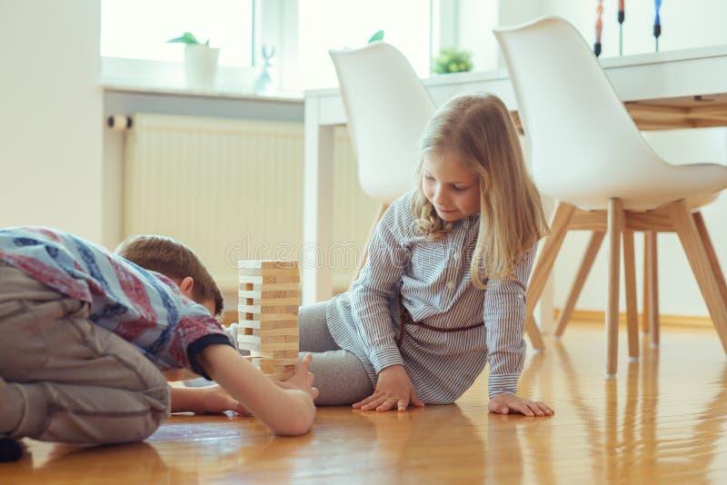 Zwei glückliche Geschwister, die zu Hause ein Spiel mit Holzklötzen spielen stockbilder