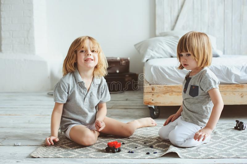 Zwei glückliche Geschwister, die zu Hause mit Spielzeugautos morgens spielen stockfotos