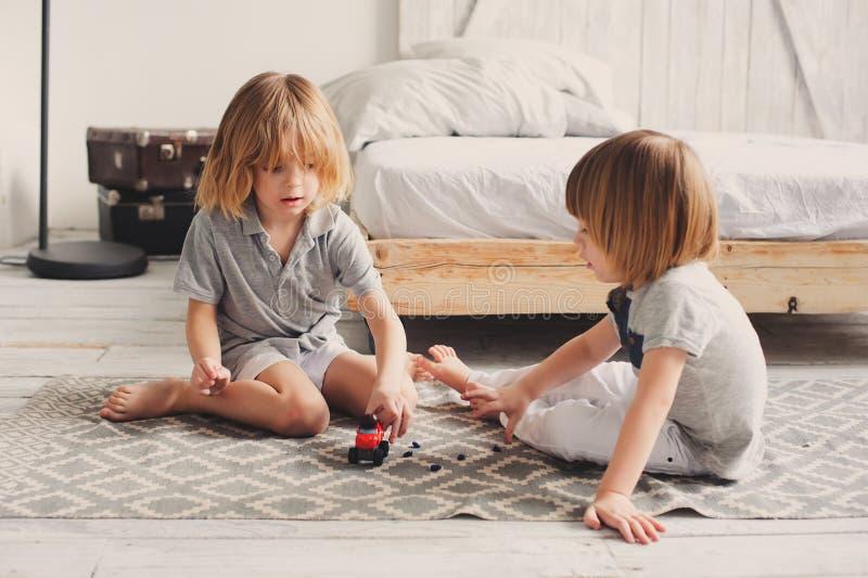 Zwei glückliche Geschwisterjungen, die zusammen zu Hause mit Spielzeugautos spielen stockbilder