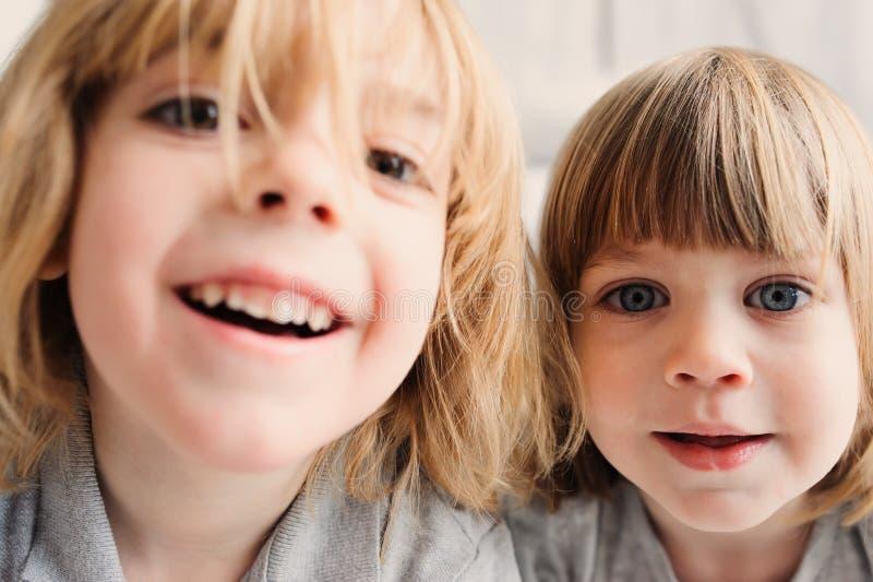 Zwei glückliche Geschwisterjungen, die zusammen zu Hause mit Spielzeugautos spielen stockfotos