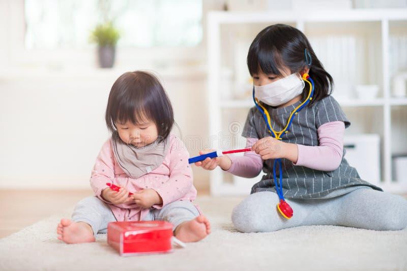 Zwei glückliche japanische Schwestern, die zu Hause mit medizinischem Satz spielen stockbilder