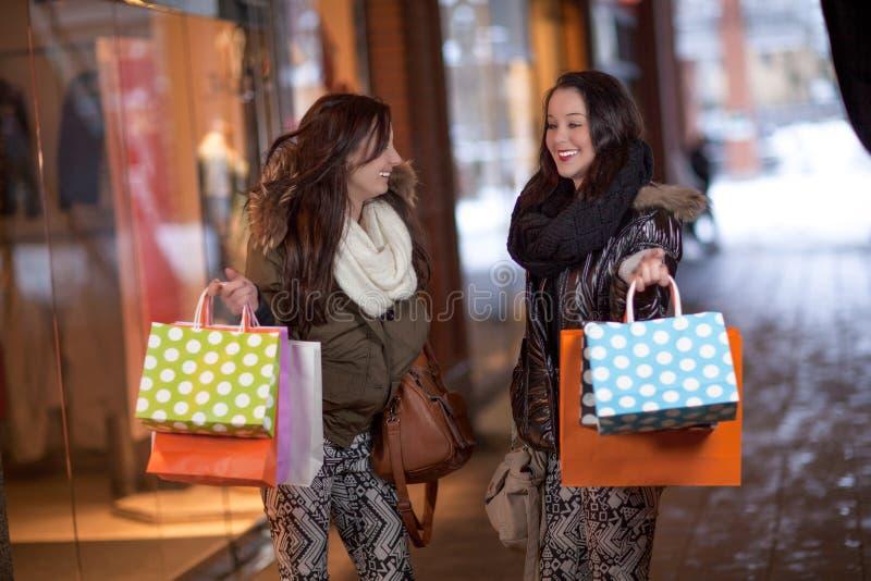 Zwei glückliche junge Frauen, die Einkaufstaschen halten lizenzfreies stockbild