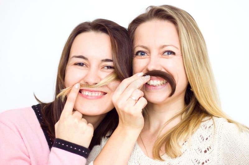 Zwei glückliche junge Freundinnen, die mit dem Haar als Schnurrbart spielen stockbilder